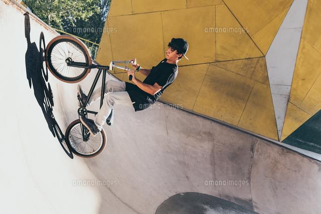 作品番号:11115076068 作品タイトル:young man riding bicycle on ramp at park