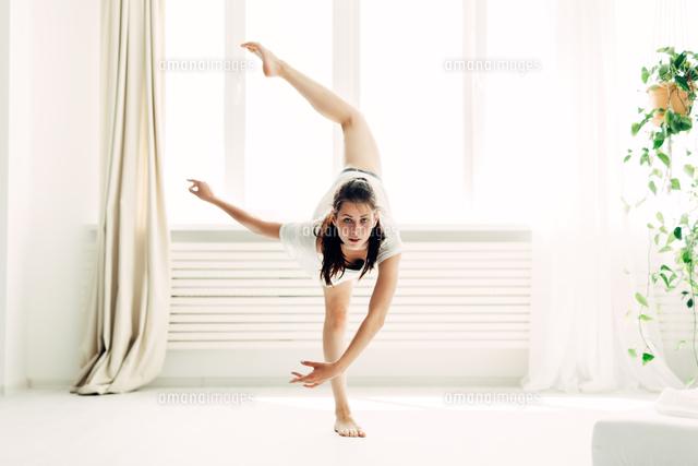 作品番号:11115076811 作品タイトル:full length portrait of young woman practicing yoga in warrior position at home