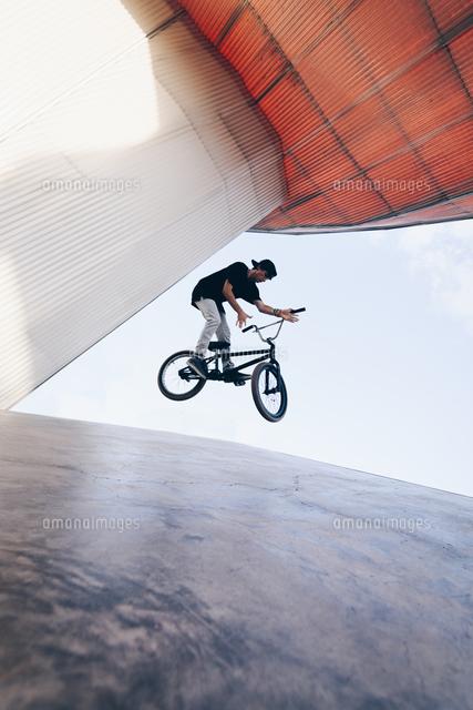 作品番号:11115077145 作品タイトル:young man riding bicycle on ramp at park