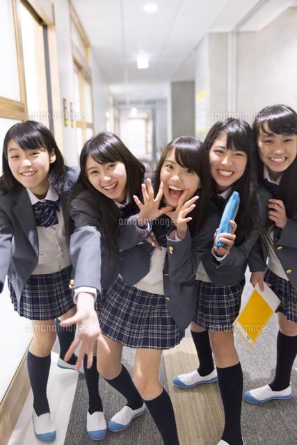学校の廊下でポーズをとる女子高...