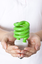 Cupped hands holding a green energy saving lightbulb