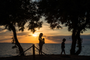 Silhouette of mother and children by water at sunset, Italy
