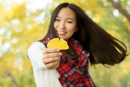 Portrait of young woman holding yellow gingko leaf in autumn park, Beijing, China