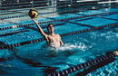 Water polo player catching ball in pool