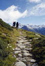 Two people hiking up a mountain path
