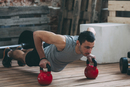 Dedicated man exercising with kettlebells at gym