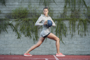 Full length of confident female athlete exercising with medicine ball