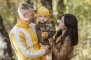 Smiling parents looking at baby boy while standing in park during autumn
