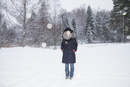 Full length portrait of mid adult woman standing on snow covered field
