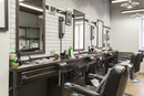 Empty chairs in front of mirrors at barber shop
