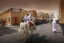 Men riding horses on Doha street, Doha, Qatar
