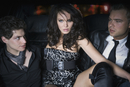 Glamorous woman in backseat of limousine with two businessmen