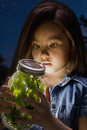 Chinese girl looking at fireflies in jar