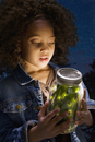African girl looking at fireflies in jar