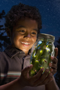 African boy looking at fireflies in jar