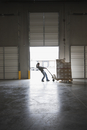 Mixed race woman pulling boxes on pallet in warehouse