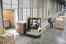 Forklift moving boxes onto truck at loading dock of warehouse