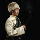 Tibetan man in traditional clothing with incense