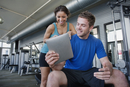 Couple using digital tablet in health club