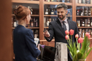 Businessman paying clerk at liquor store counter