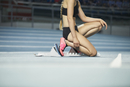 Female runner kneeling at starting block on sports track