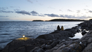 Sweden, Sodermanland, Braviken, Teenage girl (16-17) sitting with young woman on seashore at dusk