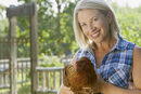 attractive middle-aged woman holding a chicken