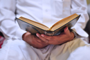 Muslim in traditional robes reading Quran