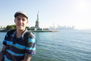 Portrait of man standing against Statue of Liberty