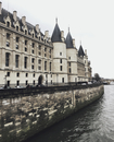 Conciergerie by Seine river against sky