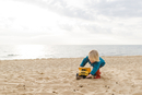 Boy playing with toy truck at beach against cloudy sky