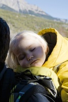 Baby girl asleep in carrier on parent's back 11001050512| 写真素材・ストックフォト・画像・イラスト素材|アマナイメージズ