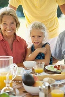 Girl and grandmother at breakfast table outdoors, cropped 11001053499| 写真素材・ストックフォト・画像・イラスト素材|アマナイメージズ