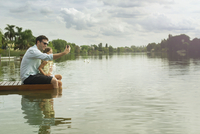 Father and daughter sitting on dock taking selfie 11001062678| 写真素材・ストックフォト・画像・イラスト素材|アマナイメージズ