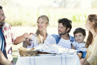 Extended family eating meal and talking together outdoors 11001063934| 写真素材・ストックフォト・画像・イラスト素材|アマナイメージズ