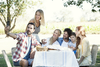 Family posing for a group photo while picnicking outdoors 11001063935| 写真素材・ストックフォト・画像・イラスト素材|アマナイメージズ