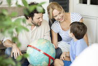 Family with one child looking at world globe together 11001064347| 写真素材・ストックフォト・画像・イラスト素材|アマナイメージズ