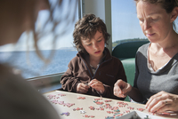 Family putting together jigsaw puzzle together 11001064470| 写真素材・ストックフォト・画像・イラスト素材|アマナイメージズ