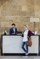 Woman looking at smartphone while waiting at reception desk 11001065352| 写真素材・ストックフォト・画像・イラスト素材|アマナイメージズ