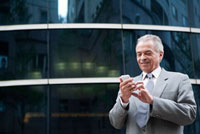 Senior Businessman holding mobile phone in front of an offic 11010044168| 写真素材・ストックフォト・画像・イラスト素材|アマナイメージズ