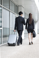 Business people walking with rolling suitcase, rear view 11010046278| 写真素材・ストックフォト・画像・イラスト素材|アマナイメージズ