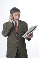 Business man holding newspaper and on the phone 11010046411| 写真素材・ストックフォト・画像・イラスト素材|アマナイメージズ