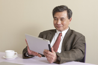 Business man holding note pad and smiling 11010046417| 写真素材・ストックフォト・画像・イラスト素材|アマナイメージズ