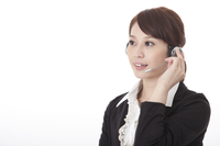 Businesswoman wearing headphone and looking away with smile 11010046544| 写真素材・ストックフォト・画像・イラスト素材|アマナイメージズ