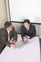 Business men sitting and looking at the laptop together 11010046556| 写真素材・ストックフォト・画像・イラスト素材|アマナイメージズ
