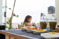 Father and daughter sitting at breakfast table on balcony, healthy food in foreground 11015251592| 写真素材・ストックフォト・画像・イラスト素材|アマナイメージズ