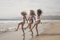 Three young women holding hands and dancing on windswept beach 11015265909| 写真素材・ストックフォト・画像・イラスト素材|アマナイメージズ