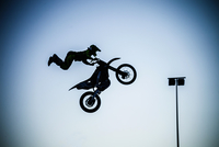 Man performing extreme stunt with motorcycle in mid air 11015267852| 写真素材・ストックフォト・画像・イラスト素材|アマナイメージズ