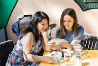 Young woman with mother and baby daughter looking at photographs at sidewalk cafe 11015269811| 写真素材・ストックフォト・画像・イラスト素材|アマナイメージズ