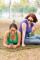 Young women on picnic blanket using smartphone looking down smiling 11015270426| 写真素材・ストックフォト・画像・イラスト素材|アマナイメージズ